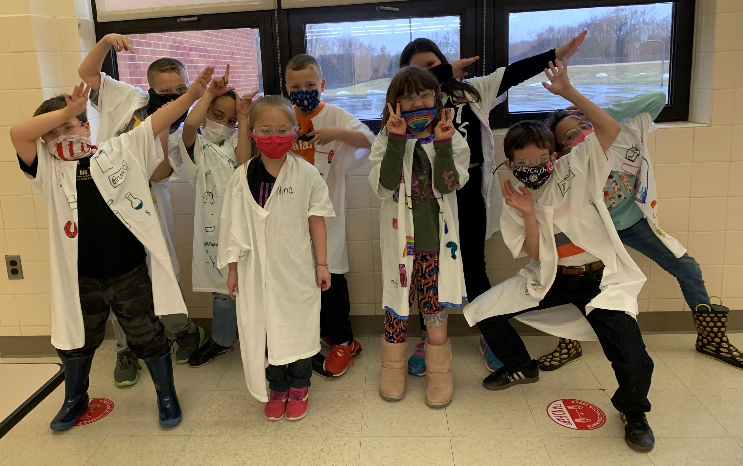 Students  from the SHINE Program show off the Lab Coats they made after a visit from WMH.